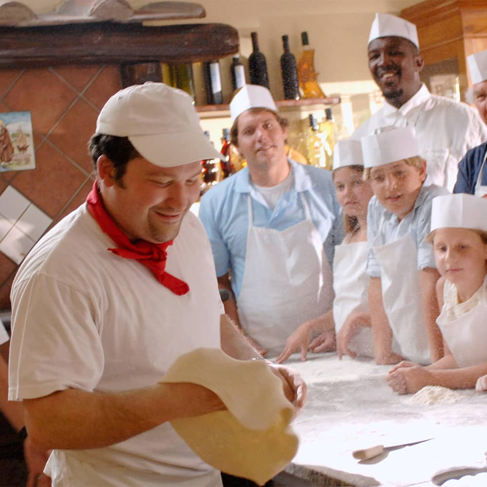 A chef shows kids how to make pizza dough