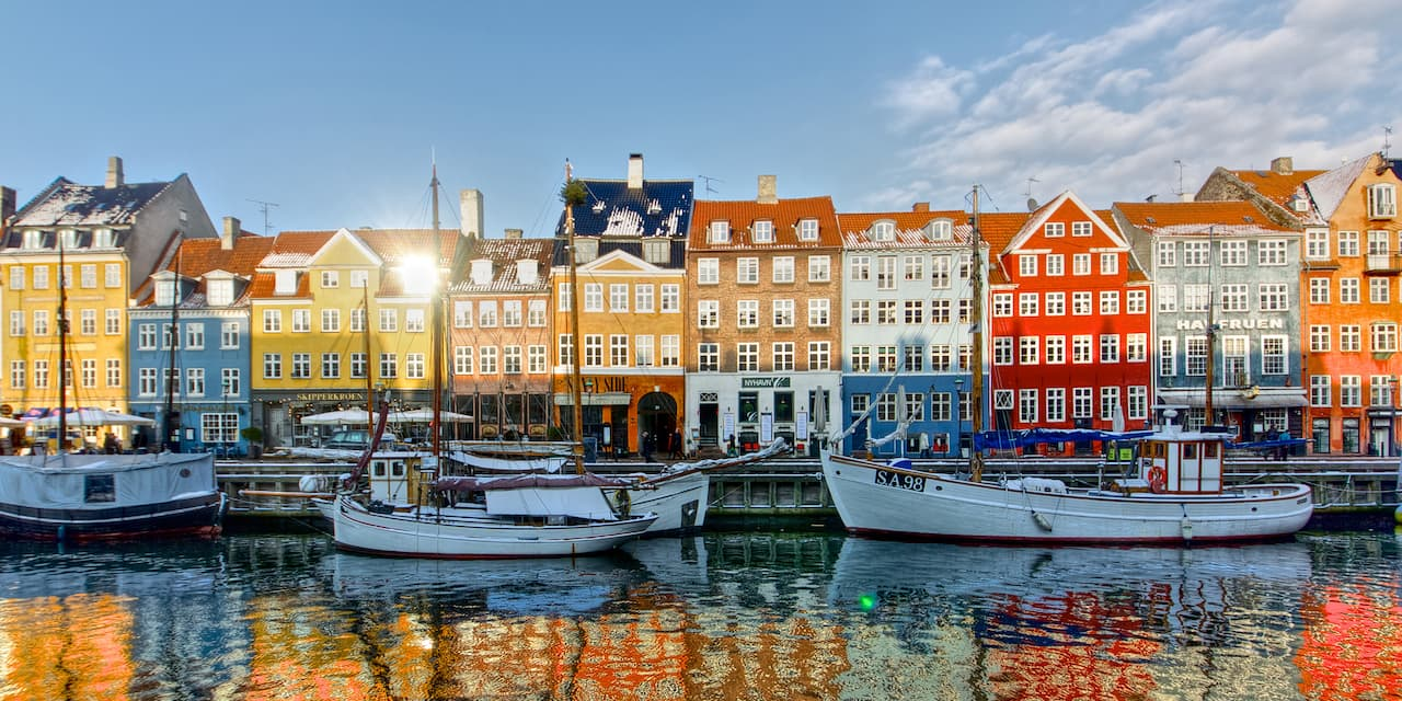 Sailboats are docked at the Copenhagen harbor near European row houses