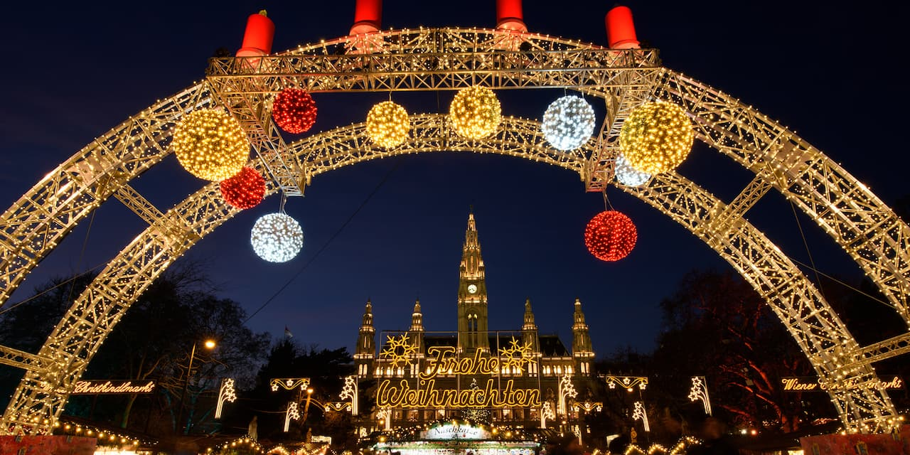 "A Christmas market in Vienna is decorated in holiday lights, including a large arc with festive balls of light hanging down and framing a large building with a lighted sign that reads: ""Frohe Weihnachten"""