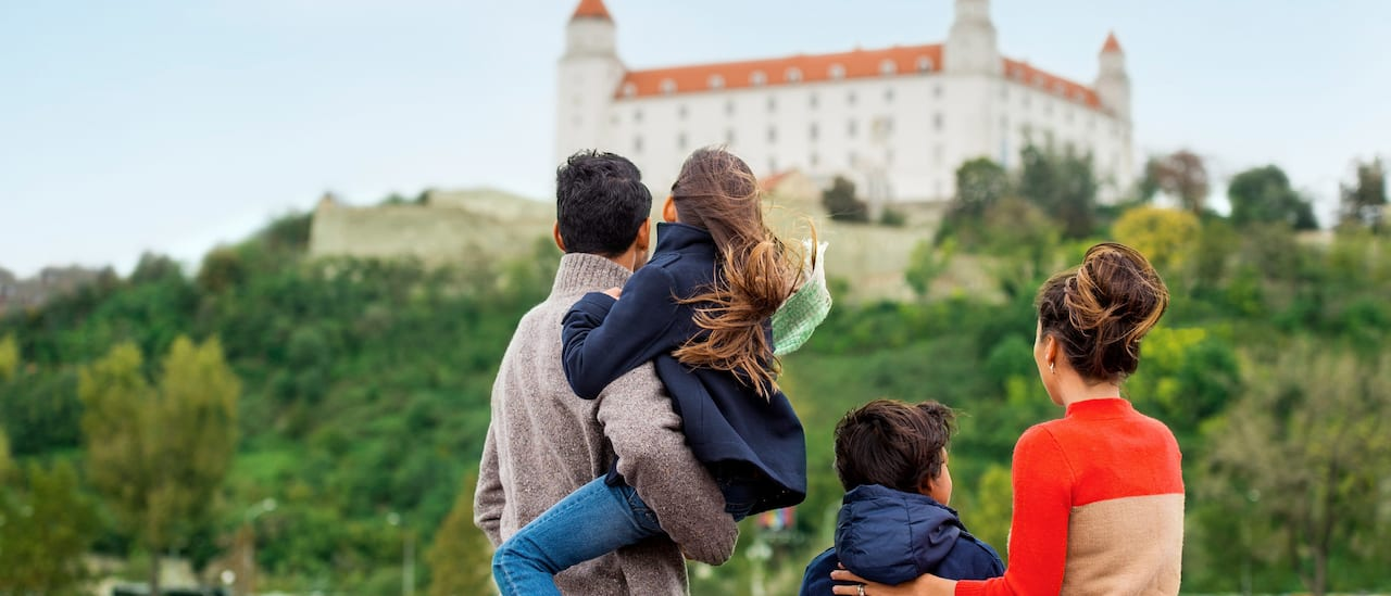 A family of 4 looks at a building on a hill