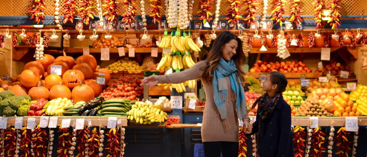 A mother and daughter shop in an outdoor store with fresh fruits and vegetables