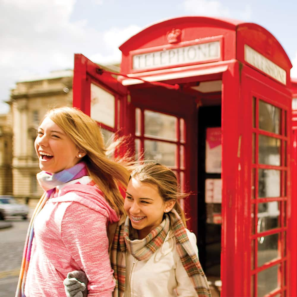 2 girls by a phone booth on the streets of London