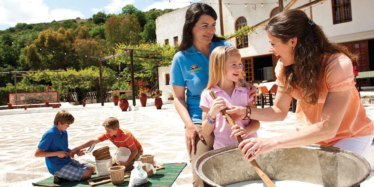 An Adventure Guide looks on as a mom and daughter stir a large pot while 2 boys play on a mat in the background