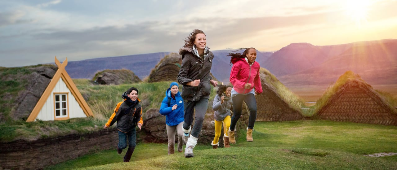 A group of kids run up a grassy hill near some turf houses