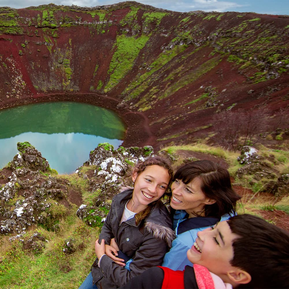 3 people sit on a bench near the water in Kerið Crater