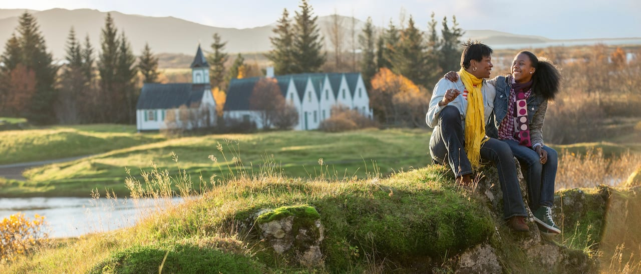 A stream winds through the trees and lush valley of Thingvellir National Park, with a church in the distance