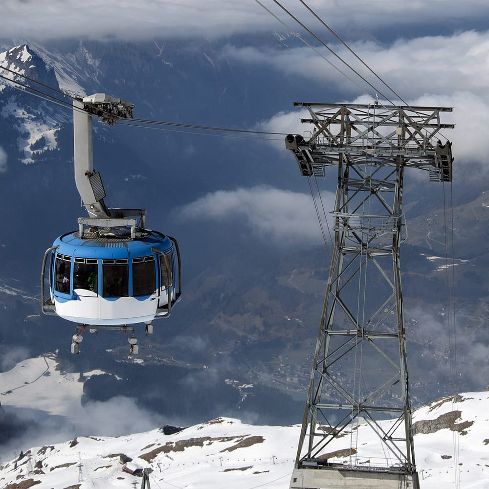 An aerial cable car rides through a region with snow covered mountains