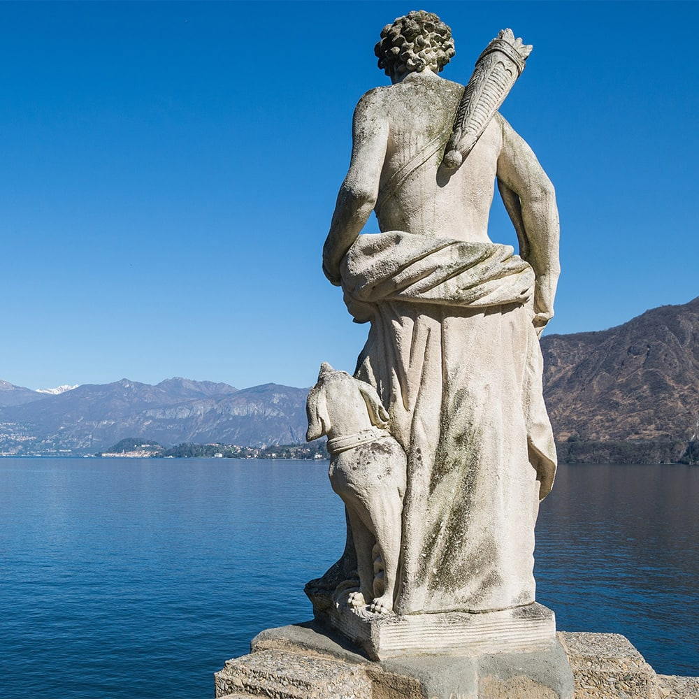 The back of a statue of a man and his dog look out over Lake Como and the surrounding mountains as a boat rides across the water