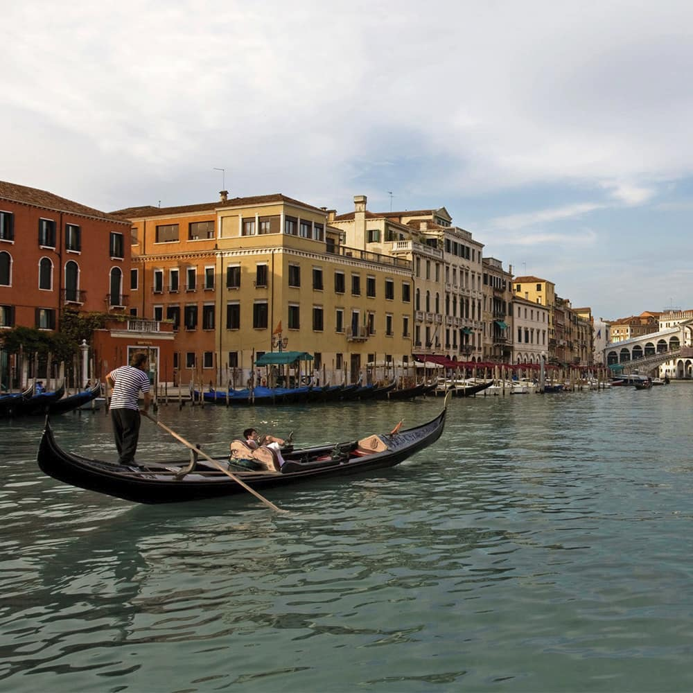A gondolier rows a man along a canal flanked by grand old buildings in Venice, Italy