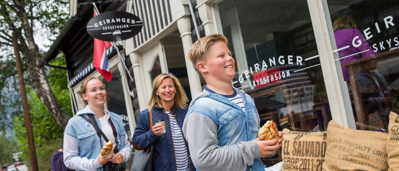 A mom, her preteen son and daughter walk past a store's sign that reads 'Geiranger,' eating pastries