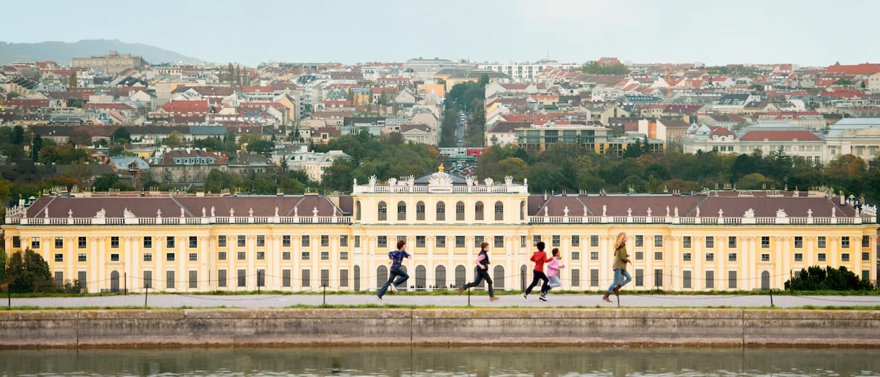 A group of kids run along the river in front of Schönbrunn Palace, with the city of Vienna in the background