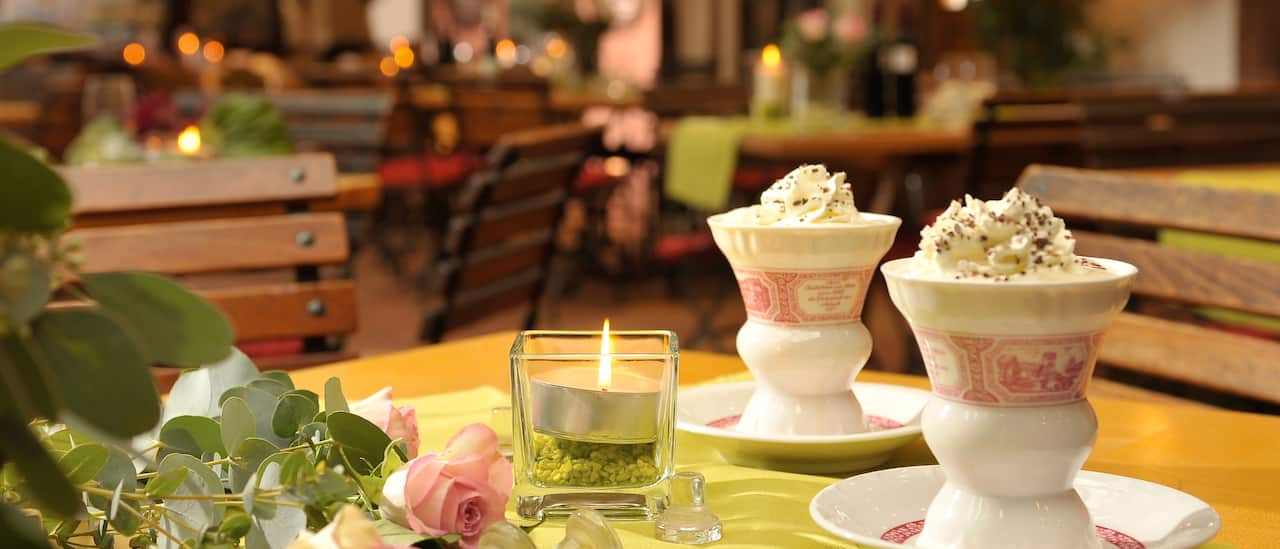 Two cups, topped with whipped cream, sit on a table with a lit candle and several roses, in a restaurant with wood slatted chairs and archways