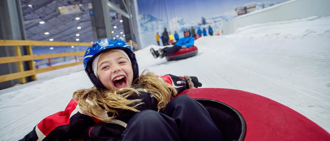 A girl thrills to tubing down a snowy indoor slope