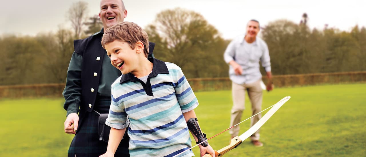 A little boy tries his hand at archery while a teacher and his father watch