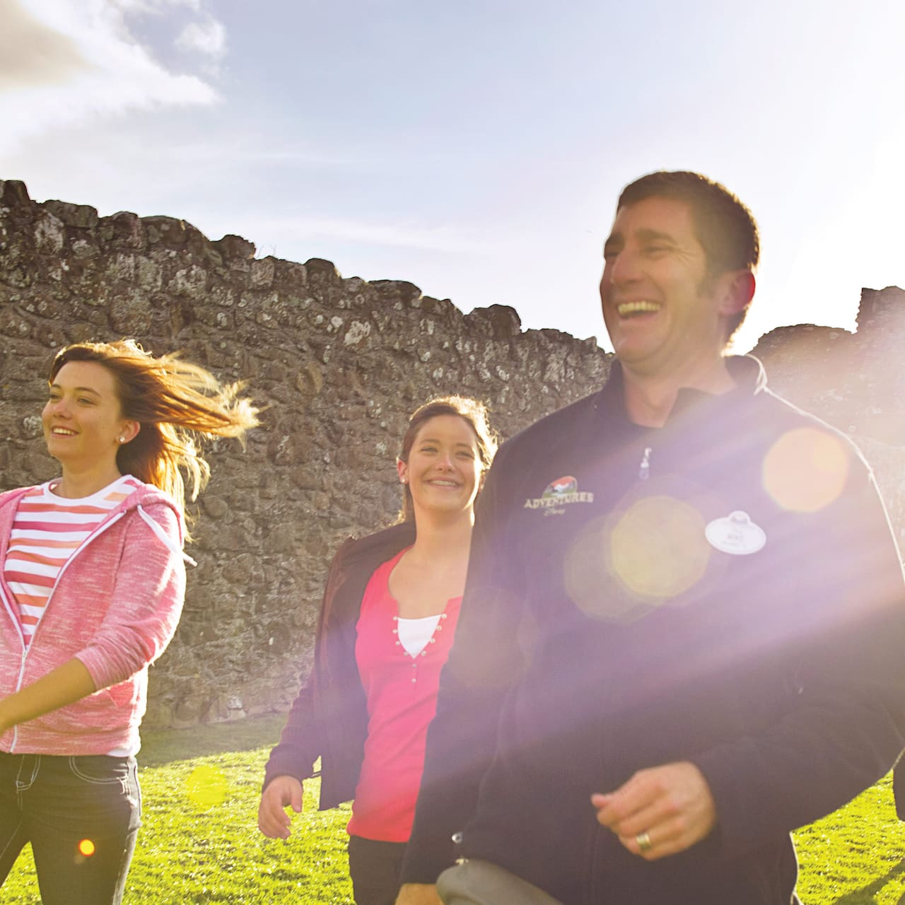 A family of 5 with girls in their early teens walks alongside the wall of an ancient Scottish ruin