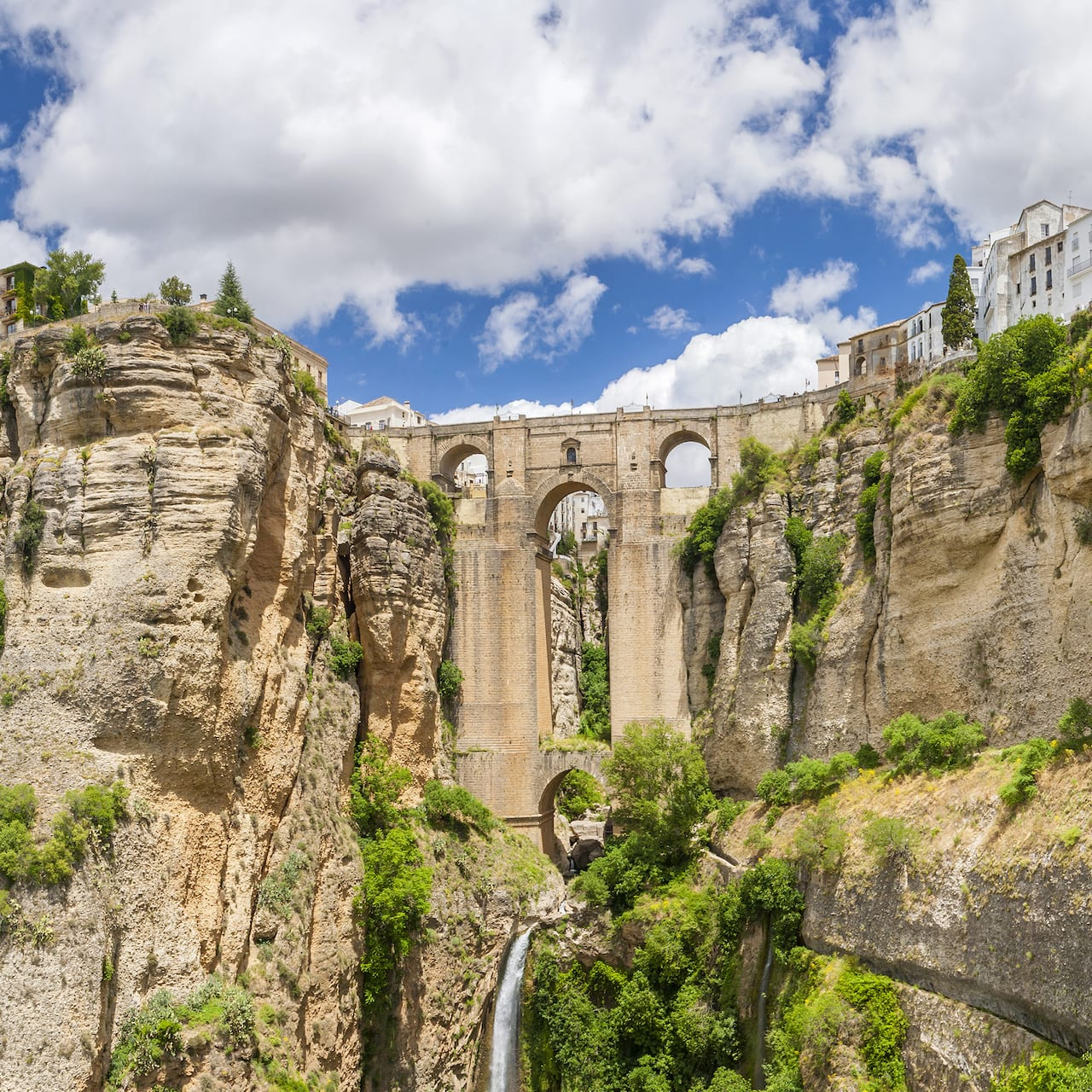 The Puente Nuevo bridge spans the gorge between 2 steep cliffs