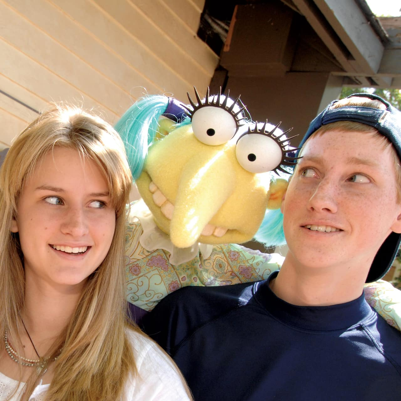 A teen boy and girl near a sign reading 'The Jim Henson Company' are surprised by a puppet