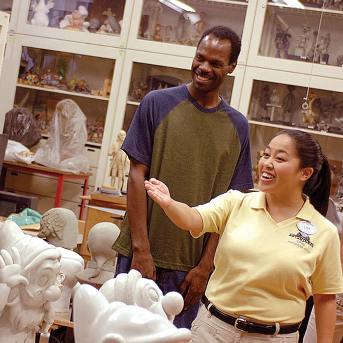 An Adventures by Disney Guide shows a couple a room filled with statues of Disney characters