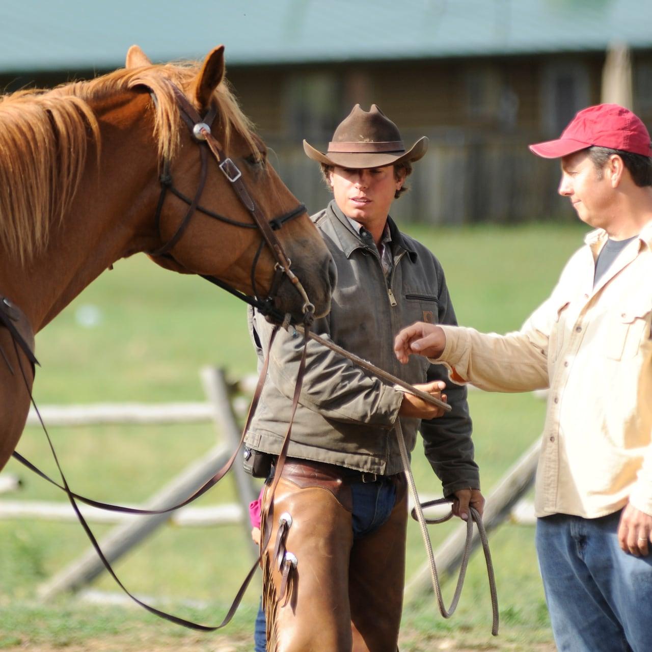 A cowboy hands a Guest the reins of a horse
