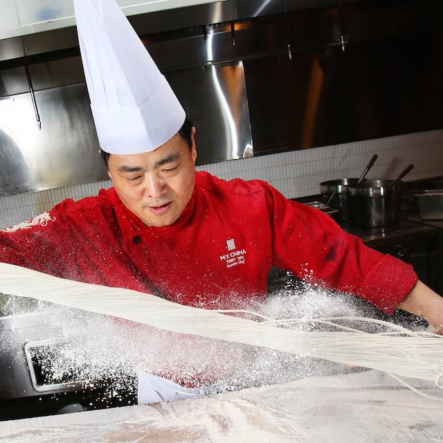 A Chinese chef with a shirt that reads 'M.Y. China' pulls dough to make noodles