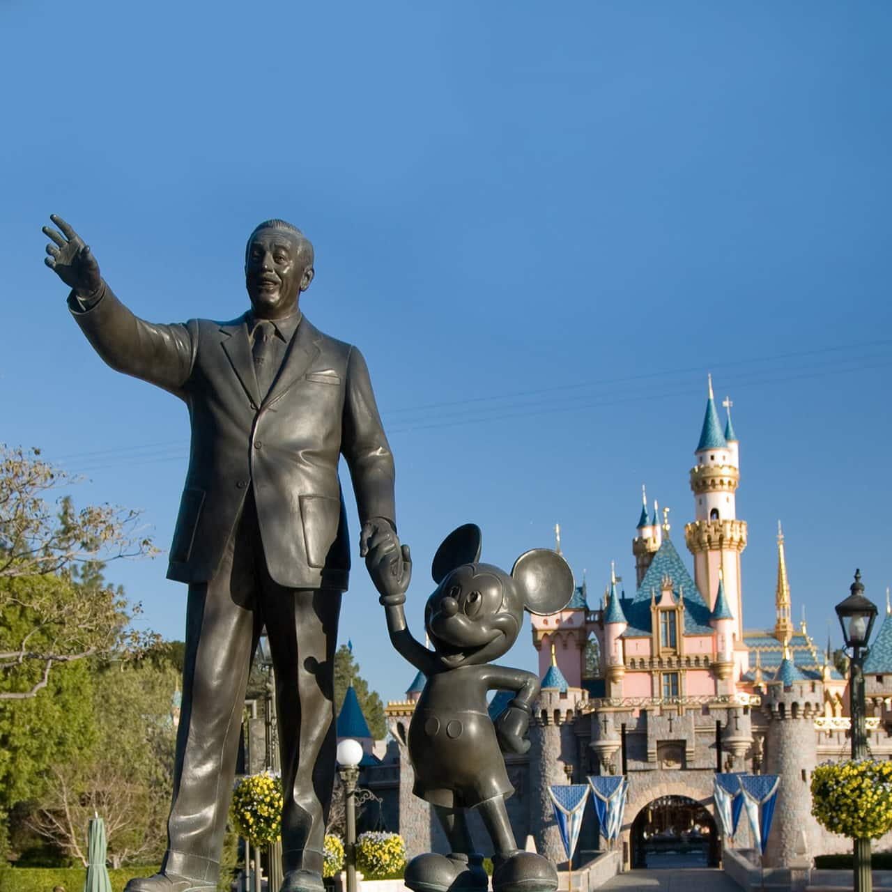 """The Disneyland Park """"Partners"""" statue featuring Walt Disney and Mickey Mouse in a bed of tulips with Sleeping Beauty Castle in the background"""