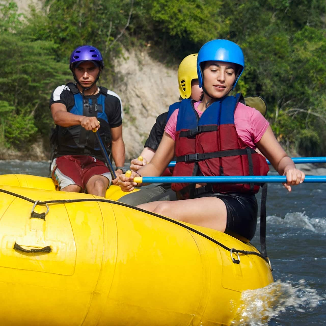 5 teenagers paddle in a whitewater raft down a river