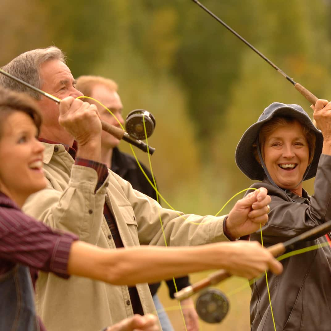 3 women and 2 men with reels in hand are fly fishing