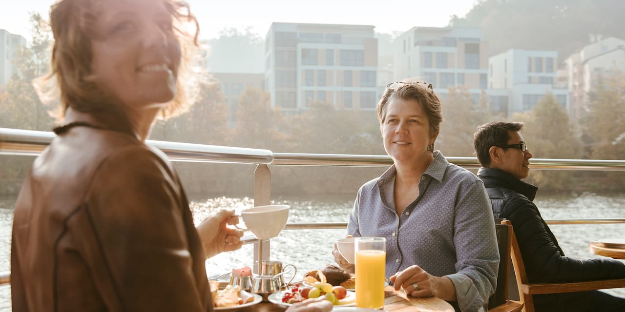 A woman holding a coffee cup looks over her shoulder during a meal with another woman at a table on the top deck of a river boat as it sails past buildings on the nearby shore