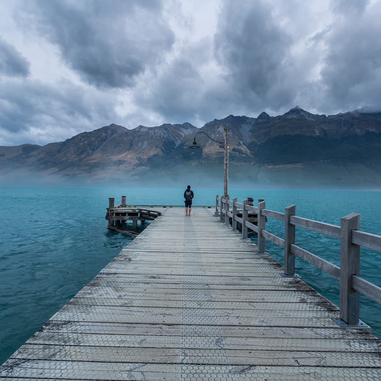 A person stands at the end of a long wooden dock that leads into the sea near a mountain range