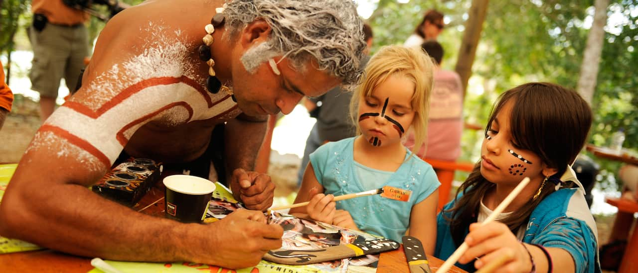 An aboriginal man shows 2 young girls wearing face paint how to decorate a boomerang