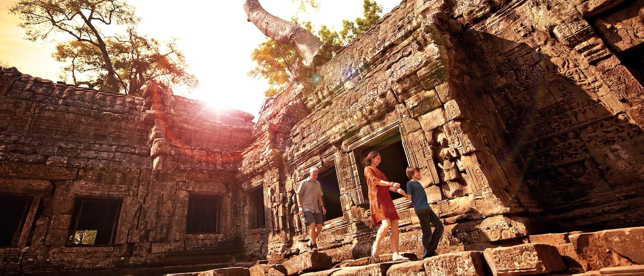 A boy holds his mother's hand with his father following as they explore an ancient temple