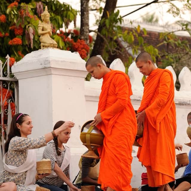 A family sits on the ground giving alms to monks dressed in traditional robes