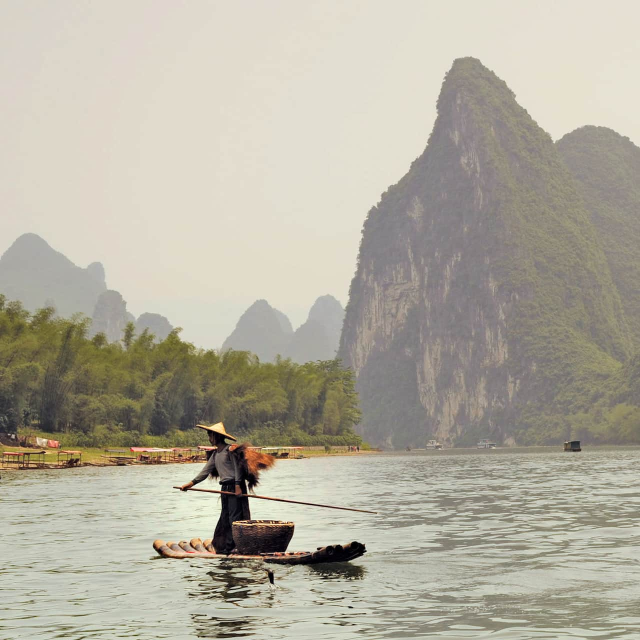 Fishermen ride on bamboo rafts along the Li River against the backdrop of spectacular scenery