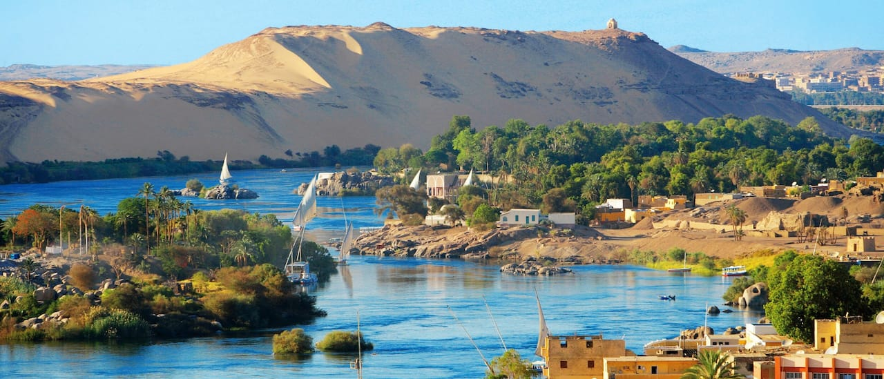 A waterway flows through a seaside village and mountainous desert region