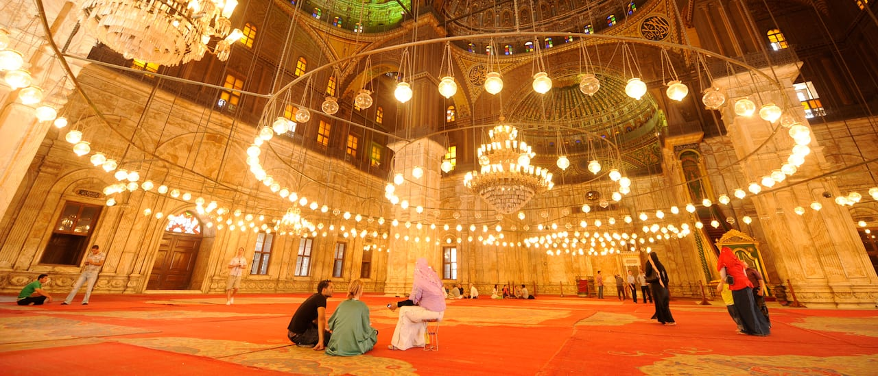 A group of people pray on a carpeted floor of a large, ornate room with a circle of lights hanging from the ceiling in the Great Mosque of Muhammad Ali