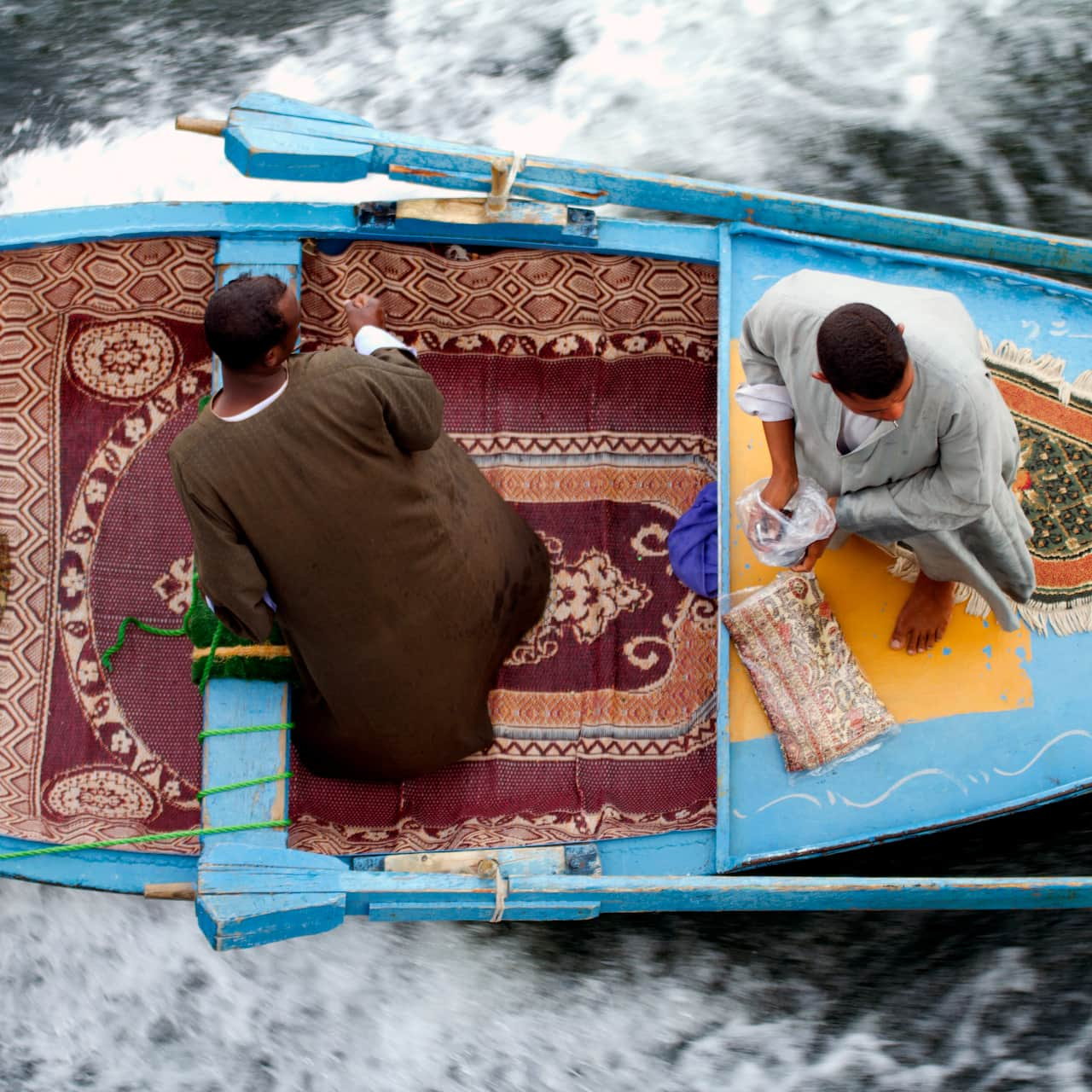 A birds-eye view of 2 people riding in a boat with rugs