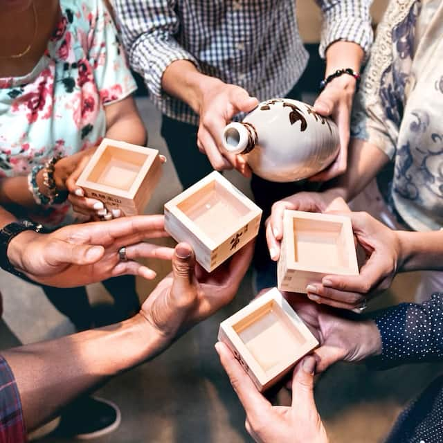 A person pours sake into the square, wooden cups of a group of smiling people