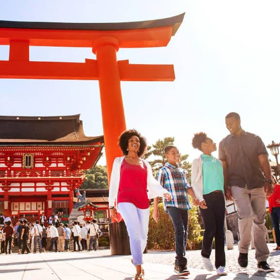 A family of 3 and an Adventure Guide walk in front of the Fushimi Inari Shrine in Kyoto, Japan