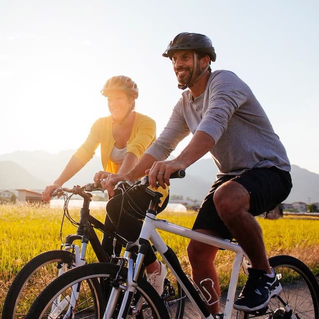 A man and woman, wearing bike helmets, ride bikes on a road in a rural area with mountains in the background