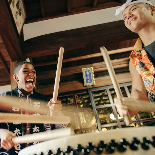A boy and his instructor are all smiles as they beat a Taiko drum with drum sticks