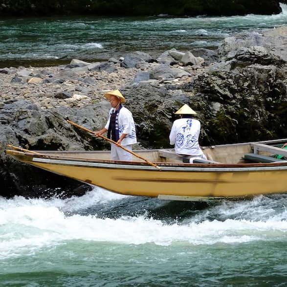 A river boat full of people is guided through rapids on the Hozugawa River