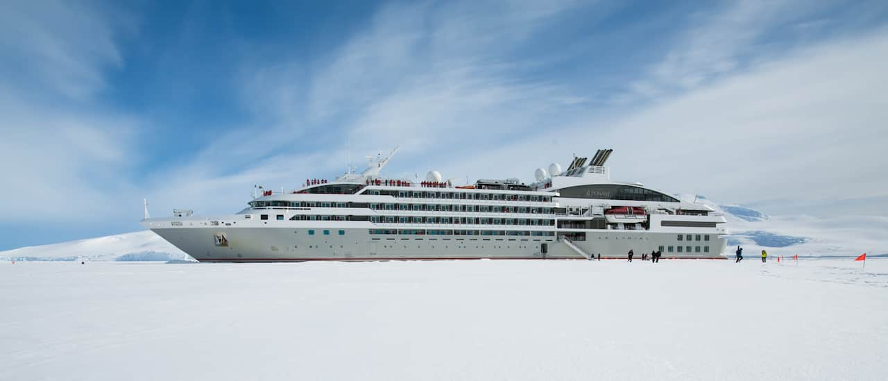 Cruise ship with disembarkation gangway to the snowy shore of Antarctica