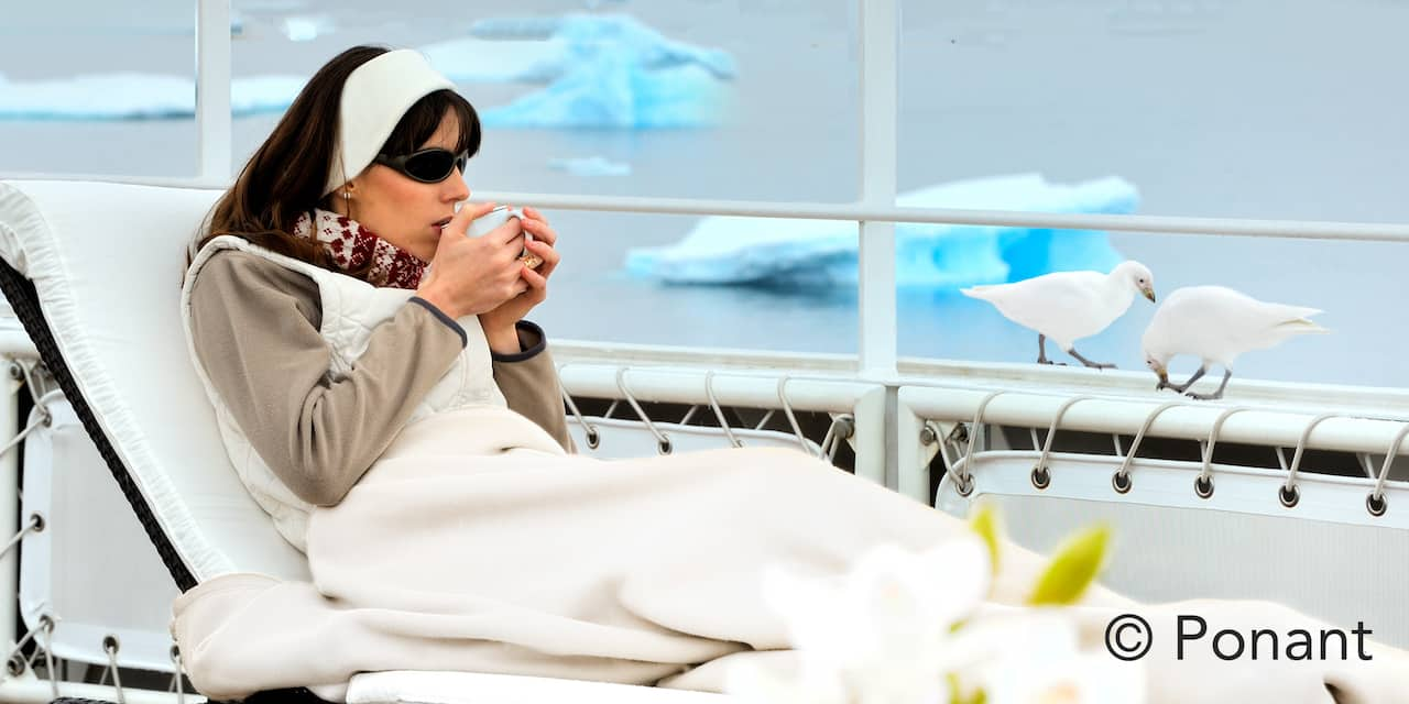 A woman sporting sunglasses and headband, lounging on a chaise lounge on the deck of a ship enjoys a cup of tea while bundled in a blanket