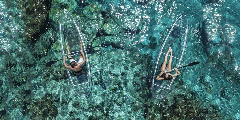 Two people kayaking in glass bottom kayaks on ocean water