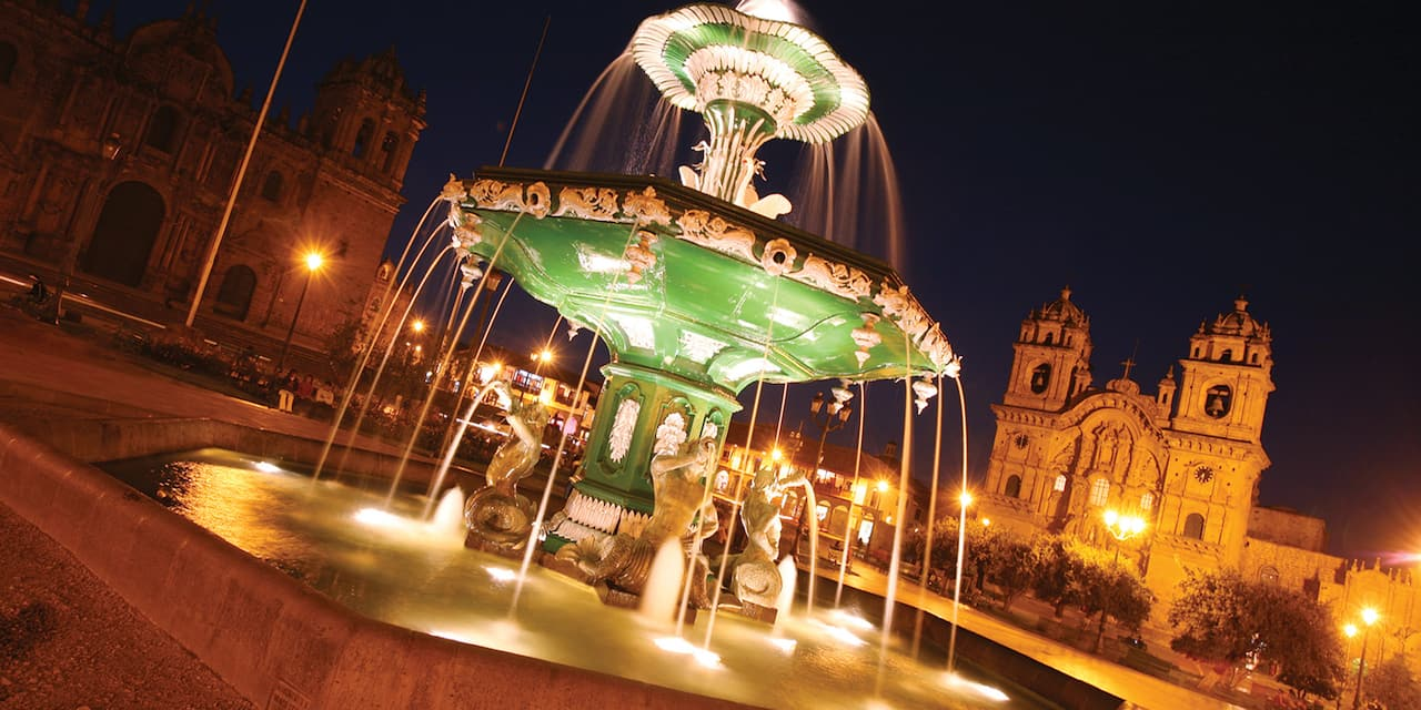 A grand water fountain in a plaza near a cathedral