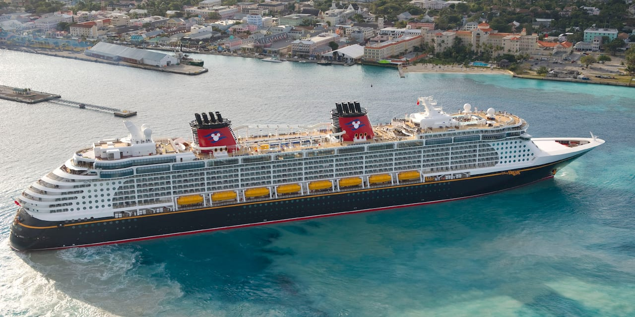 A Disney cruise ship sails in the waters near a city