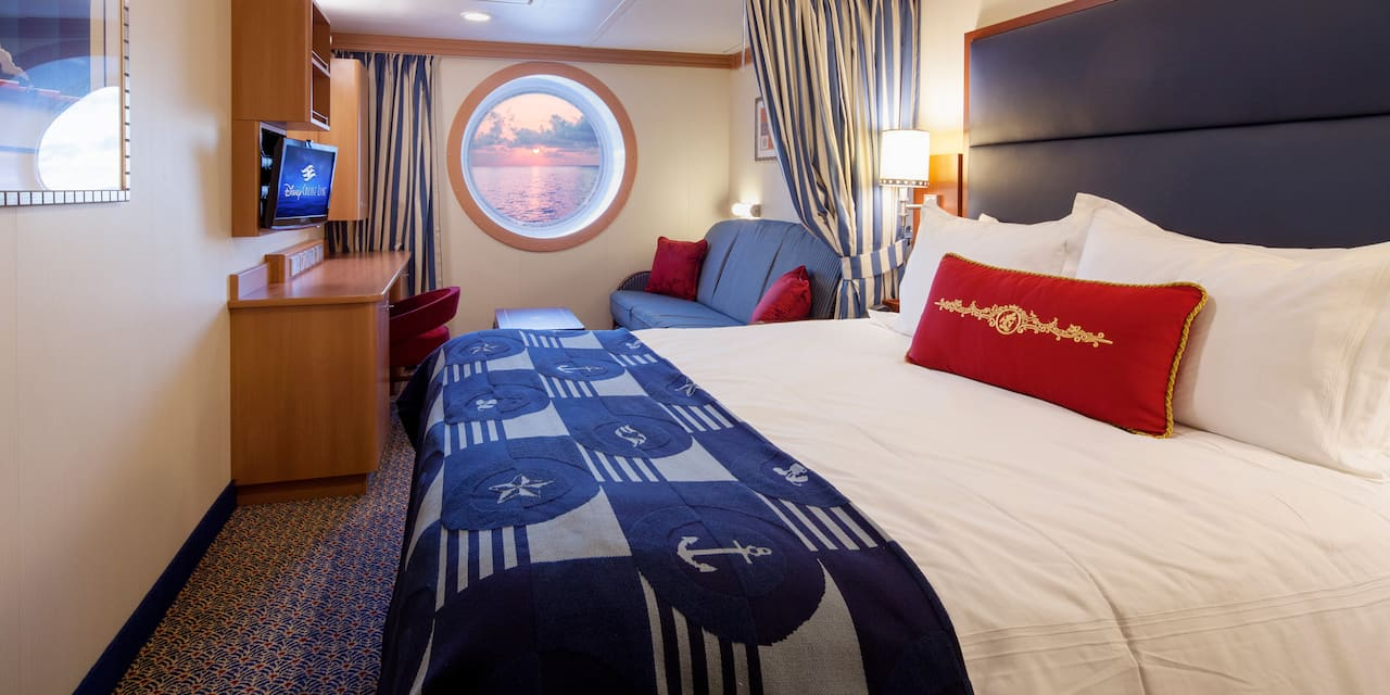 The bed and circular window in a stateroom of a Disney Cruise Line ship