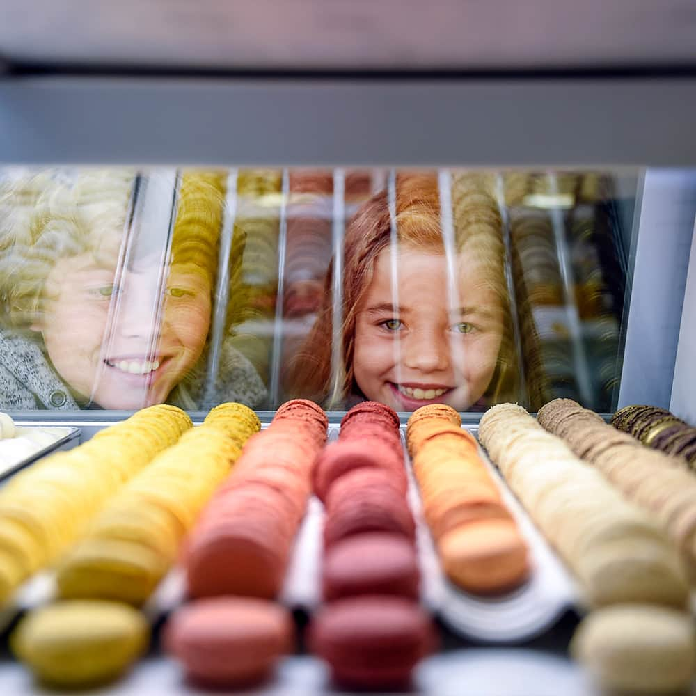 A young boy and girl are all smiles as they look through a glass display case filled with a variety of macarons at a patisserie