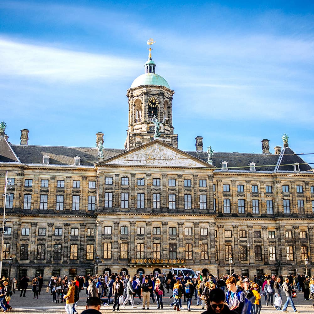 A crowd of people in front of the Royal Palace of Amsterdam