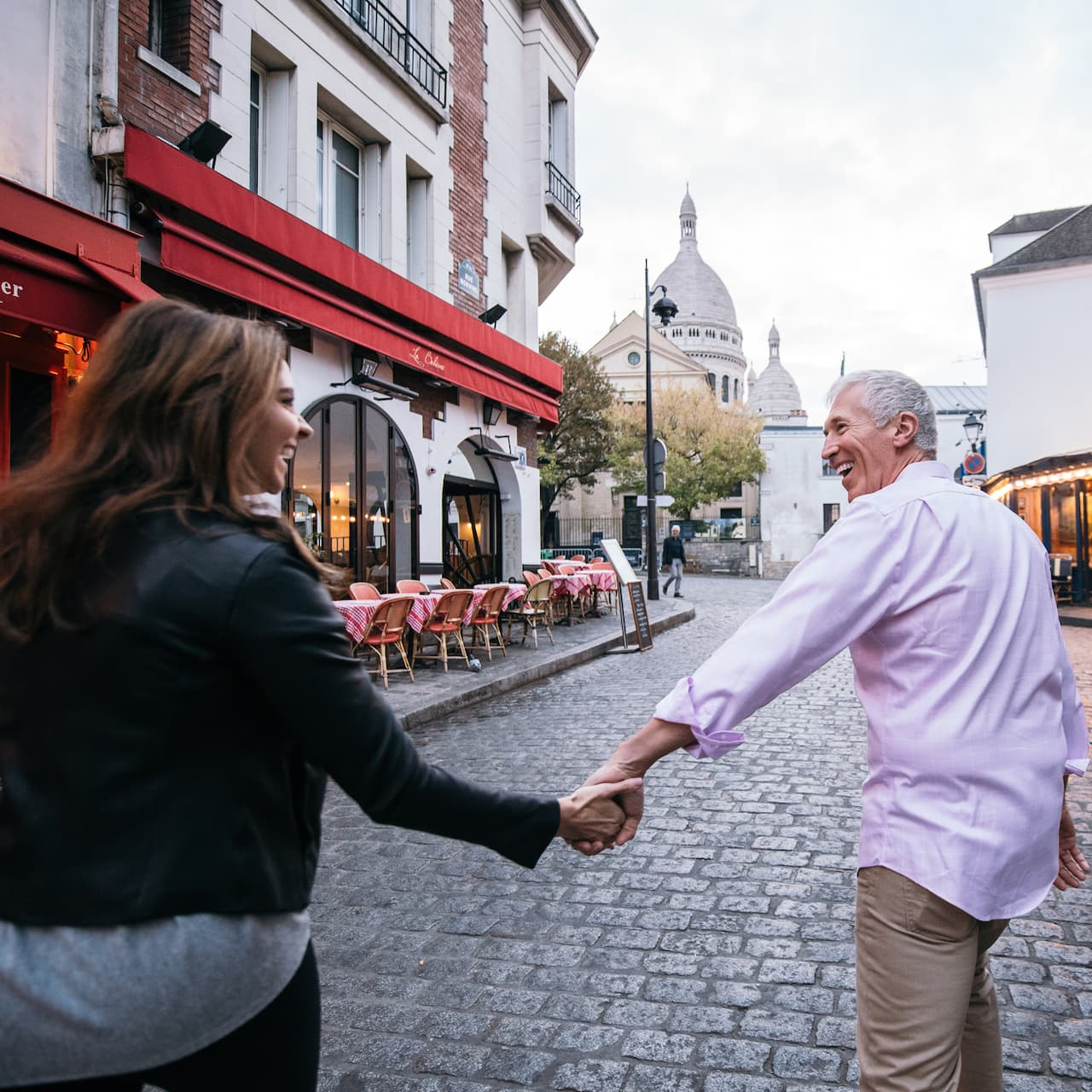 A couple walks past outdoor cafés on the cobblestone streets of Montmartre, France with the domed Sacré-Cœur basilica in the background